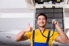 The repairman repairing ceiling air conditioning unit. Repairman repairing ceiling air conditioning unit Royalty Free Stock Photography
