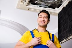 The repairman repairing ceiling air conditioning unit. Repairman repairing ceiling air conditioning unit Stock Photos