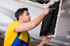 The repairman repairing ceiling air conditioning unit. Repairman repairing ceiling air conditioning unit Royalty Free Stock Photo
