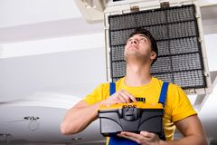 The repairman repairing ceiling air conditioning unit. Repairman repairing ceiling air conditioning unit Stock Images