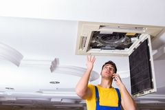 The repairman repairing ceiling air conditioning unit. Repairman repairing ceiling air conditioning unit Stock Photo