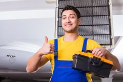 The repairman repairing ceiling air conditioning unit. Repairman repairing ceiling air conditioning unit Royalty Free Stock Images