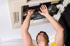 The repairman repairing ceiling air conditioning unit. Repairman repairing ceiling air conditioning unit Stock Image