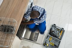 Repairman Repairing Dishwasher In Kitchen Stock Image