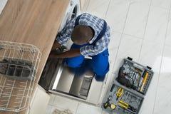 Repairman Repairing Dishwasher In Kitchen Stock Image