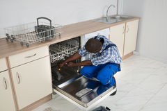 Repairman Repairing Dishwasher In Kitchen Royalty Free Stock Images