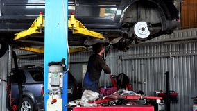 Repairman repairing exhaust system on lifted up sedan car in car repair shop. Repairman repairing exhaust system on a lifted up sedan car in a car repair shop stock video