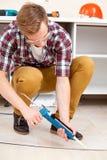 Repairman repairing the floor Stock Image
