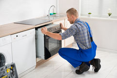 Repairman Repairing Oven. Young Repairman In Overall Repairing Oven In Kitchen Royalty Free Stock Image