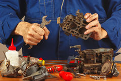 Repairman repairing parts of old automobile engine in workshop Royalty Free Stock Photography