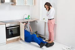 Repairman Repairing Pipe While Woman In The Kitchen Stock Photo