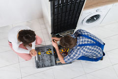 Repairman Repairing Refrigerator Stock Photo