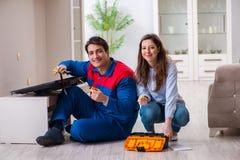 The repairman repairing tv at home. Repairman repairing tv at home Stock Photography