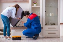 The repairman repairing tv at home. Repairman repairing tv at home Royalty Free Stock Image
