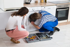 Repairman Repairing Washer In Front Of Woman Royalty Free Stock Photography