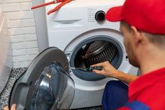 Repairman repairing washing machine door royalty free stock photo