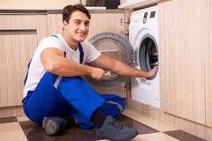 The repairman repairing washing machine at kitchen Royalty Free Stock Images