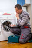 Repairman is repairing a washing machine on the white background. Entering malfunction stock photo