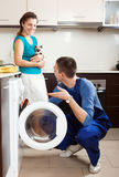 Repairman repairing a washing machine for young  woman Stock Images
