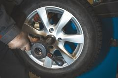 Repairman replaces and balancing car tyre wheel on special balancer equipment tool in car repair service. Close up stock images