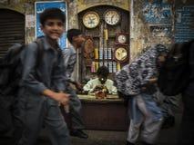 Repairman. School children passing by the watch Repairman, Sadar, Karachi Stock Photography
