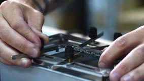 Repairman'sens händer griper den lilla chipseten i last för att reparera och löda beståndsdelar arkivfilmer