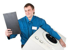 Repairman servicing washing machine Royalty Free Stock Images