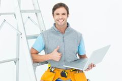 Repairman showing thumbs up sign while using laptop Stock Image