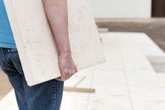 Repairman with slab. Closeup of repairman carrying concrete slab royalty free stock photo
