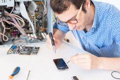 Repairman som ändrar den brutna smartphoneskärmen i tjänste- mitt Arkivfoton