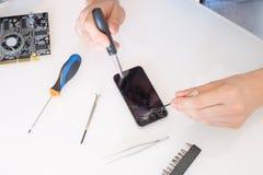 Repairman som ändrar den brutna smartphoneskärmen i tjänste- mitt Arkivbilder