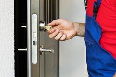 Repairman som arbetar med dörrlåset royaltyfri bild
