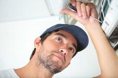 Repairman som arbetar på betingande enhet för luft Arkivbilder