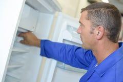 Repairman som arbetar på kylskåpet arkivbilder