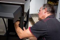 Repairman som monterar ett utomhus- grillfestgaller Fotografering för Bildbyråer