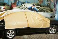 Repairman som sandpapprar biltaket Arkivbilder