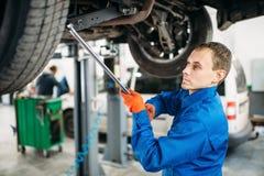 Repairman sprawdza zawieszenie, samochód na dźwignięciu zdjęcie royalty free