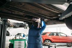 Repairman sprawdza zawieszenie, samochód na dźwignięciu zdjęcia royalty free