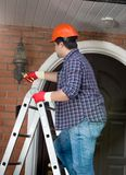Male repairman standing on stepladder and repairing outdoor lamp. Repairman standing on stepladder and repairing outdoor lamp Royalty Free Stock Photo