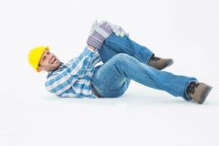 Repairman suffering from knee pain. Full length of repairman suffering from knee pain while lying against white background Stock Photography