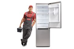 Repairman with a toolbox leaning against an open fridge. Full length portrait of a repairman with a toolbox leaning against an open fridge isolated on white Royalty Free Stock Images