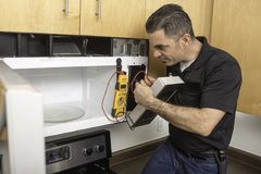 Appliance Technician Troubleshooting Microwave Stock Photos