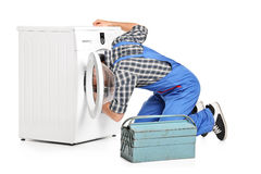 Repairman trying to fix a washing machine stock photos