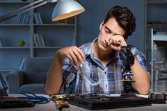 The repairman trying to repair laptop with miscroscope. Repairman trying to repair laptop with miscroscope Stock Image