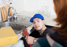 Repairman in uniform  repairing a running water Stock Images