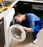 Repairman in uniform repairing washing machine Stock Photo