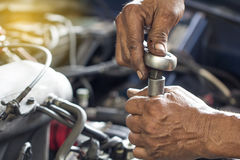Repairman use tool fixing car engine. Royalty Free Stock Photo