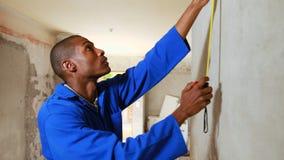 Repairman using measuring tape
