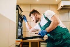 Repairman w mundurze sprawdza piekarnika, technik zdjęcia stock