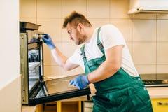 Repairman w mundurze sprawdza piekarnika, technik obrazy stock